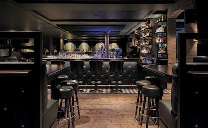 Tortue Hamburg bar noir, black leather bar stools, black woodwork, dark lighting