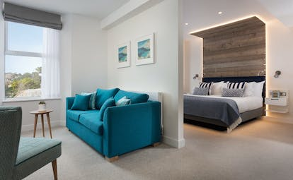 St Michael's Resort large bedroom with bed and separate living room with turquoise sofa