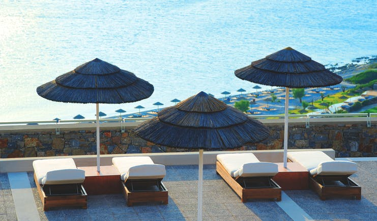 Blue Palace Greece balcony terrace sun loungers and palm umbrellas