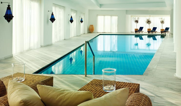 Blue Palace Greece indoor pool with blue lamps and loungers