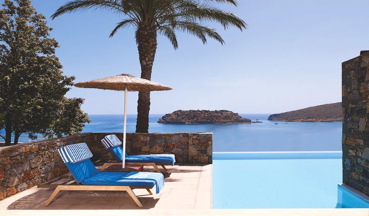 Blue Palace Greece outdoor pool loungers and sea view