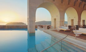 Blue Palace Greece outdoor pool decked seating area with large archways