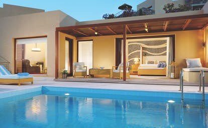 Blue Palace Greece suite pool sitting room with large windows and outdoor swimming pool with lounger