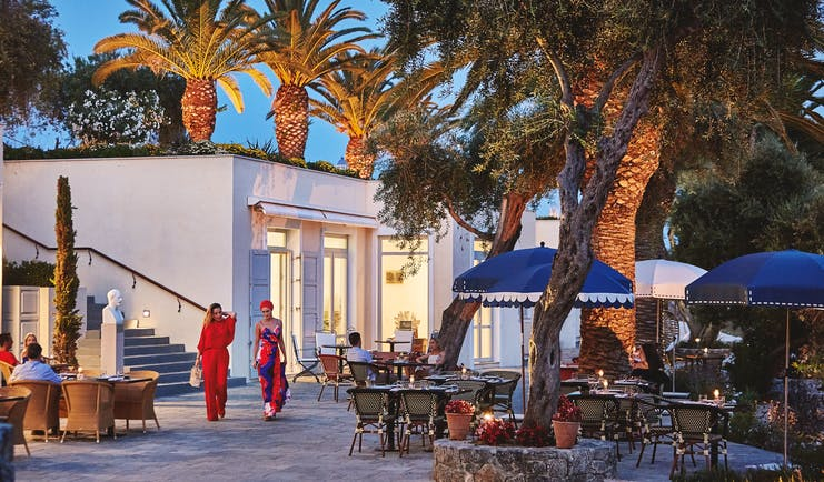 Courtyard dining at night with palm trees Corfu Imperial
