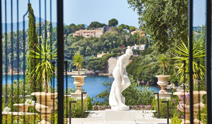 Gardens with palms and fountains and statues at the Corfu Imperial