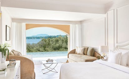 White room with open doors and pool and sea views Corfu Imperial