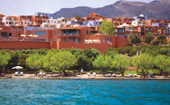 Domes of Elounda Greece exterior panorama several terracotta buildings near hills and a beach