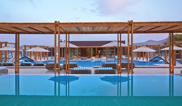 Domes of Elounda Greece outdoor pool with umbrellas