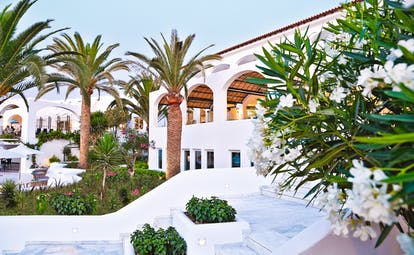 Grecotel Caramel Greece exterior white building with archways and palm trees