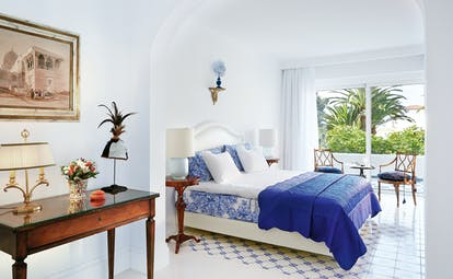 Grecotel Caramel Greece junior suite bedroom with blue and white tiled floor and balcony