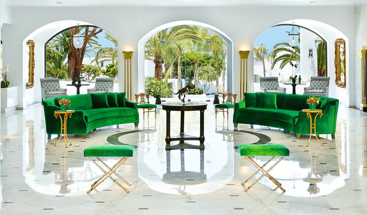 Grecotel Caramel Greece lounge area with two green sofas and archways with palm trees