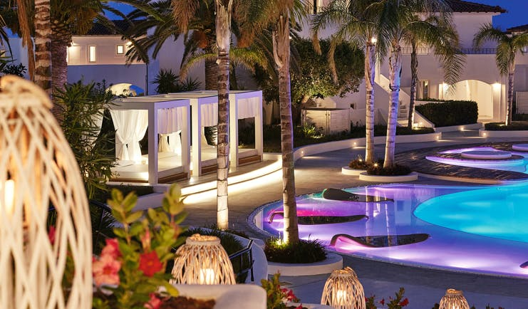 Grecotel Caramel Greece outdoor pool night with coloured lights in the water