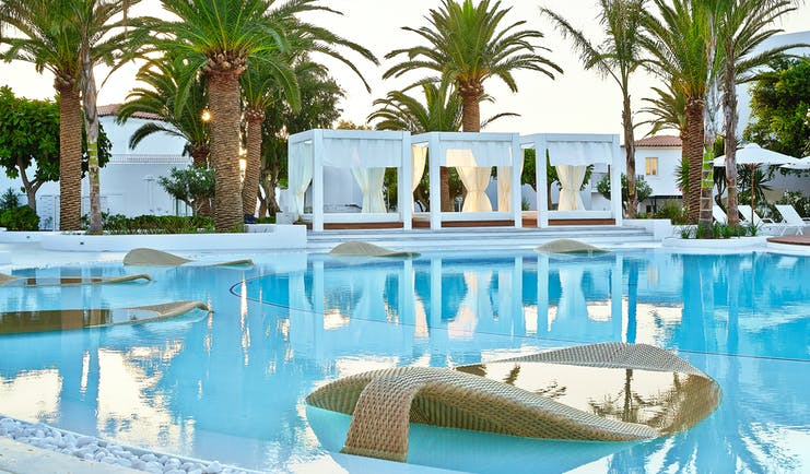 Grecotel Caramel Greece outdoor pool with leaf shape loungers in pool and canopied loungers