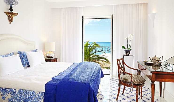 Grecotel Caramel Greece suite bedroom blue and white tiled floor desk and sea view balcony