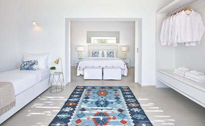 Large white room with extra bed and open wardrobe with blue rug