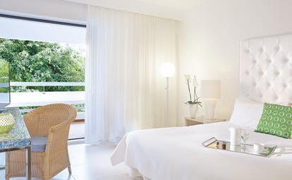 Grecotel White Palace whte room with rattan chair