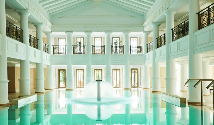 Grecotel Mandola Rosa Greece indoor pool roman style white building fountain