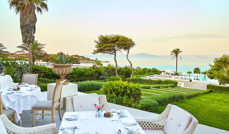 Grecotel Mandola Rosa Greece outdoor dining area overlooking lawn and sea