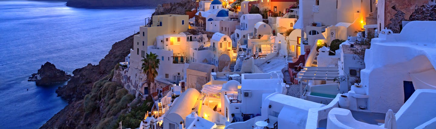 Sunset over the famous white houses and buildings on Santorini's coastline