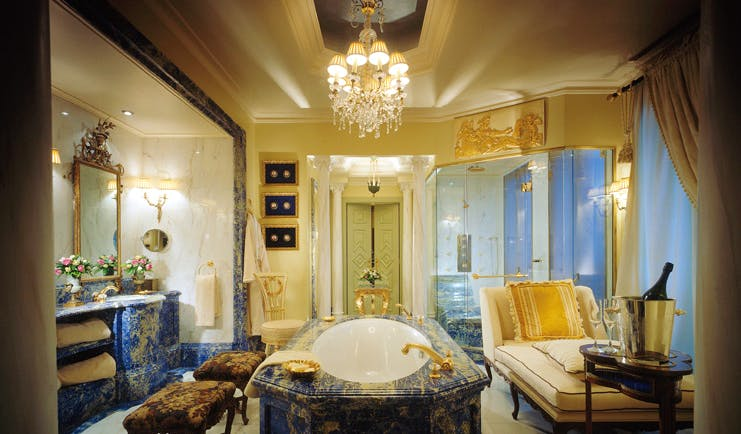 Hotel Grande Bretagne Greece bathroom opulent decor chandelier marble free standing bath chaise longue vanity unit