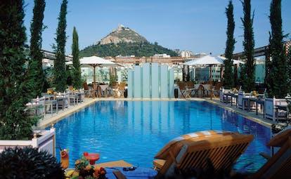 Hotel Grande Bretagne Greece outdoor pool sun lounger umbrellas mountain view