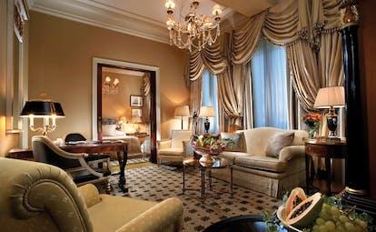 Hotel Grande Bretagne Greece suite sitting room opulent decor armchairs sofa chandelier archway to bedroom