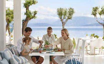 Ikos Dassia Greece Ouzo restaurant family eating outside with sea view
