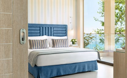 Ikos Oceania Greece deluxe family suite bedroom with balcony and sea views