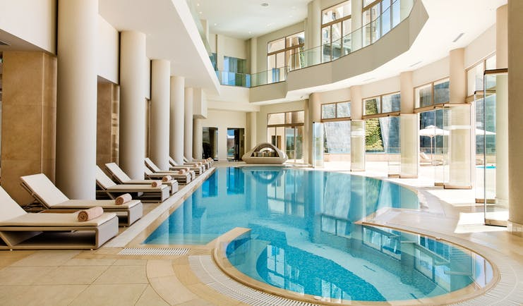 Ikos Oceania Greece indoor spa pool with loungers and large windows