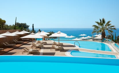 Ikos Oceania Greece infinity pool with white umbrellas and sun loungers