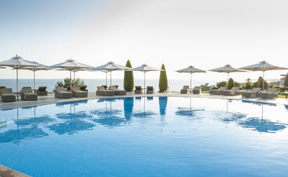 Ikos Oceania Greece outdoor swimming pool with sun loungers umbrellas and sea view