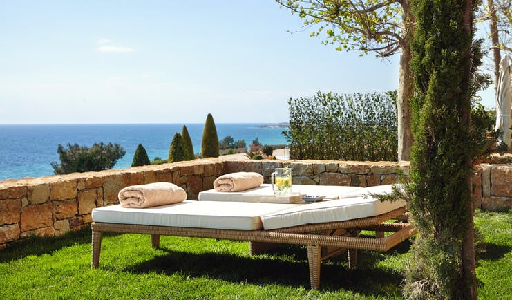 Ikos Oceania Greece private garden with two sun loungers and sea view