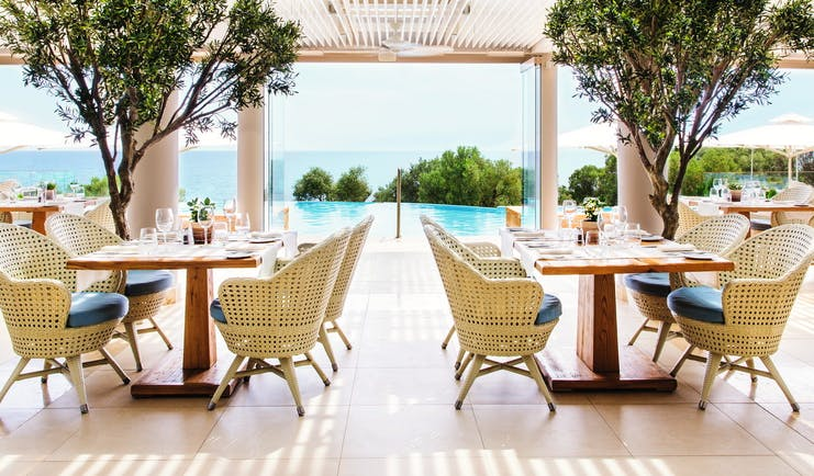 Ikos Oceania Greece Provence restaurant outdoor veranda dining area with pool and sea views