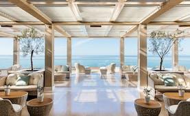 Ikos Oceania Greece veranda restaurant outdoor lounge area with large windows and sea views
