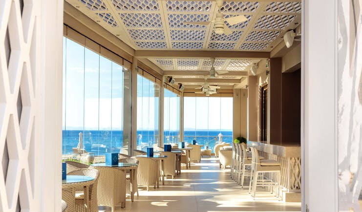 Helios bar at the Ikos Olivia with large window panneled walls looking over the ocean and white chairs and tables set up