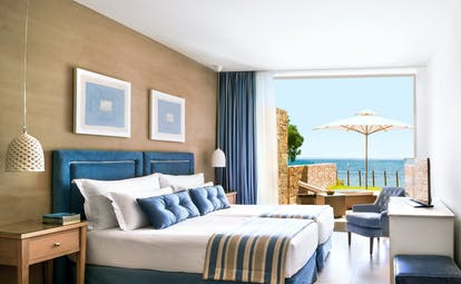 Room at the Ikos Olivia with large bed, paintings on the walls, and double doors opening up onto a terrace overlooking the sea