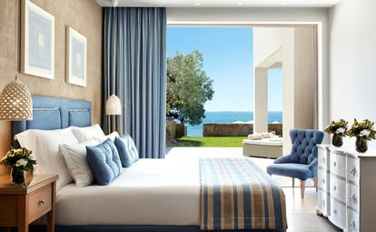 Inside one of the bedrooms of a deluxe two bedroom bungalow suite on the beachfront with large doors opening onto a terrace leading onto the beach