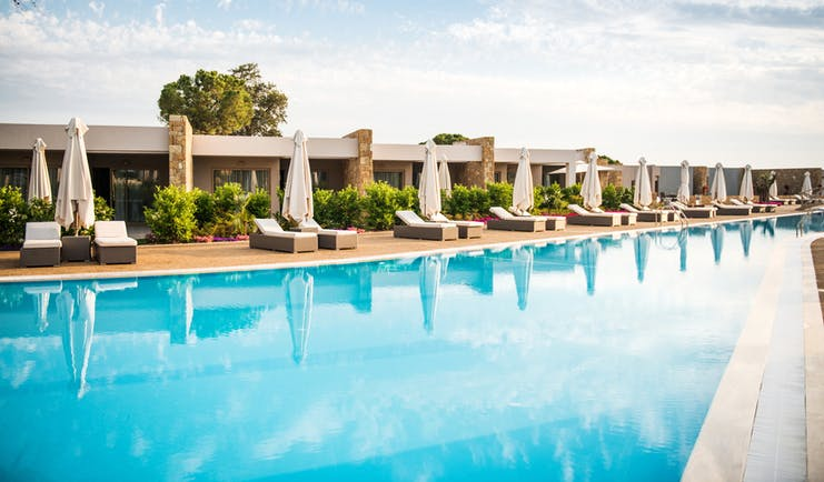 Deluxe pool at the Ikos Olivia with sun beds set up around it
