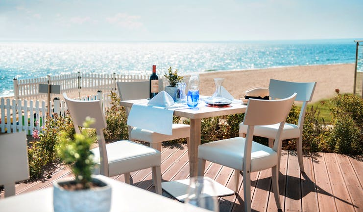 Fresco italian restaurant at the Ikos Olivia, showing an outdoor seating area on wooden decking, overlooking the beach and sea