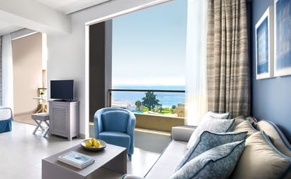Junior suite at the Ikos Olivia with double bed, blue sofa and armchair, blue colour scheme and double doors opening up onto a seaview