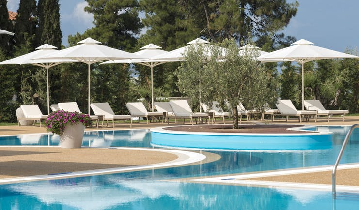 Main pool at the Ikos Olivia with white sun beds and umbrellas set up surrounding it