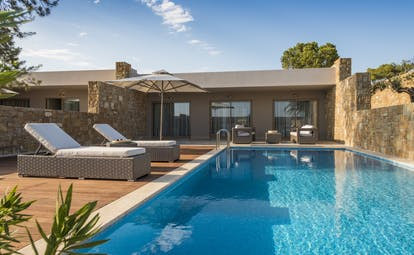 Exterior of a deluxe two bedroom bungalow suite at the Ikos Olivia showing a private pool with deck chairs around the edge