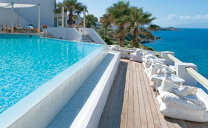 Mykonos Blu Greece Grecotel outdoor pool with covered deck lounging area and sea view