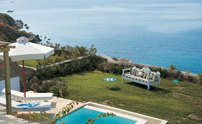 Mykonos Blu Greece Grecotel private terrace view pool with sun loungers and umbrella garden area and sofa