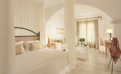 Mykonos Grand Hotel Greece bedroom with white drapes and seating area with sofa