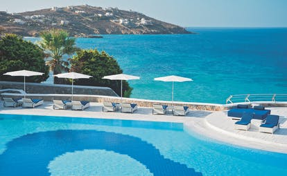 Mykonos Grand Hotel Greece exterior pool with sun loungers looking over the sea