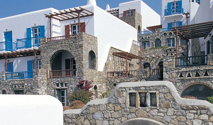 Mykonos Grand Hotel Greece exterior white and stone buildings with blue shutters and balconies