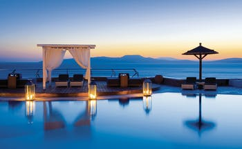 Mykonos Grand Hotel Greece main pool with decked area and cabana at night