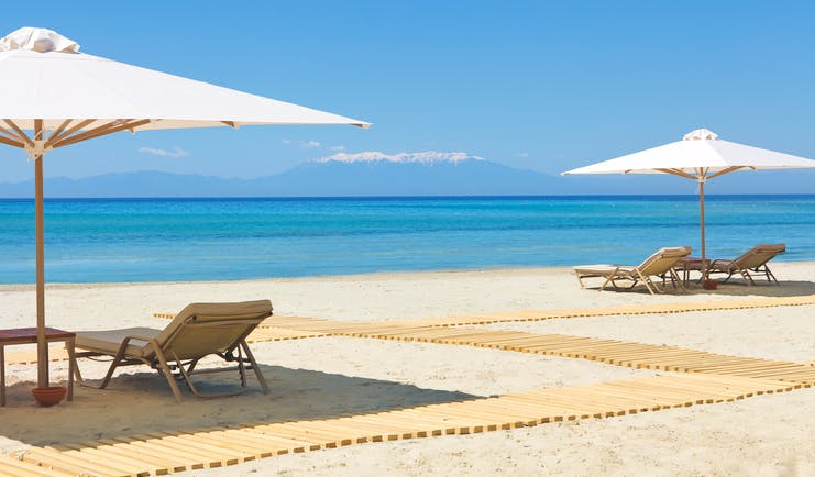 Porto Sani Greece beach with sun loungers and white umbrellas
