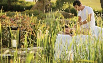 Porto Sani Greece spa man giving a woman a massage in a garden area